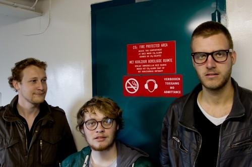 De Redactie voor de redactiekamer. Van links naar rechts: Joop den Toonder, Claudio Beerschot, deur van de redactiekamer, Thomas de Looier.